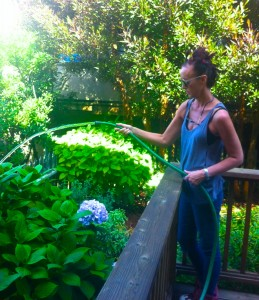 Me, in my new yard, watering flowers and plants I don't know the  names of.